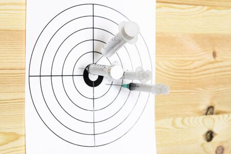 Four medical syringe hit the center of the rifle target. On the wooden background. Humor concept of therapy.