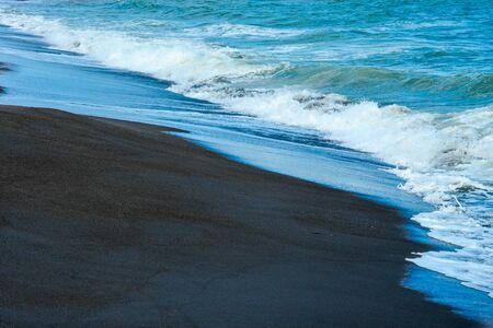 Beach on the Tyrrhenian Sea from the black volcanic sand. Ladispoli, Italy.