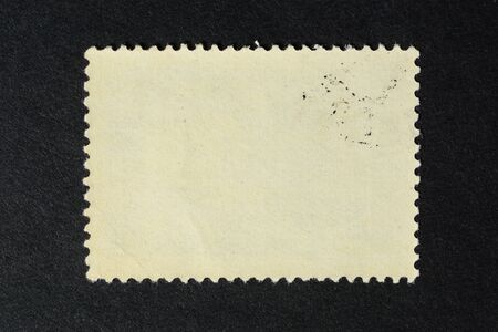 Blank vintage postage stamp on black background. Mockup with perforations for your picture, text or design.