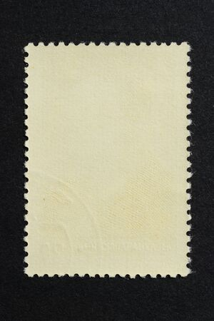 Blank vintage vertical postage stamp on black background. Mockup with perforations for your picture, text or design 2.