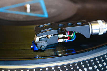 Audiophile cartridge mounted in shell played on turntable. Vinyl records equipment. Macro, close-up
