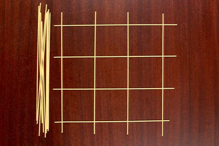 Italian pasta. Game grid maade from raw spaghetti for playing Tic Tac Toe game or Xs and Os. The dry capellini on a brown wood table.