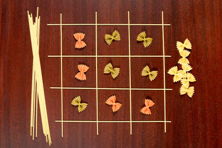 Italian pasta. Tic Tac Toe or Xs and Os game made from raw spaghetti, green yellow and red farfalle. Dry macaroni and capellini on a brown wood table.