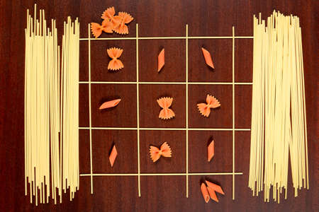 Italian pasta. Tic Tac Toe or Xs and Os game made from raw spaghettiwith red farfalle and penne. Dry macaroni and capellini on a brown wood table.