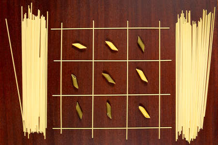 Italian pasta. Tic Tac Toe or Xs and Os game made from raw spaghetti, green and yellow penne. Dry macaroni and capellini on a brown wood table.