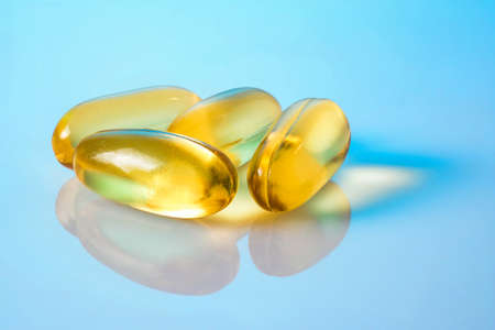 Omega 3 capsules on the gloss blue surface with reflections. Four fish oil capsules, close up macro high resolution.