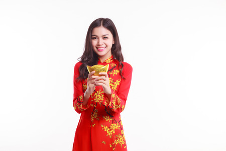 Beautiful Vietnamese woman with red ao dai holding lucky new year ornament - stack of gold on white background photo