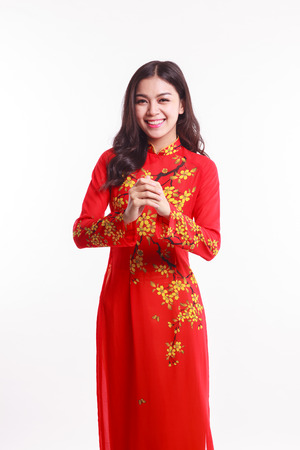 Beautiful Vietnamese woman with red ao dai holding lucky decorate object for celebrate lunar new year on white background