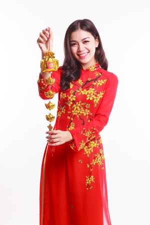 ao: Beautiful Vietnamese woman with red ao dai holding lucky decorate object for celebrate lunar new year on white background