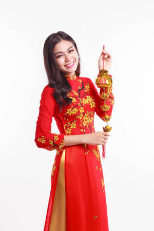 Beautiful Vietnamese woman with red ao dai holding lucky decorate object for celebrate lunar new year on white background photo