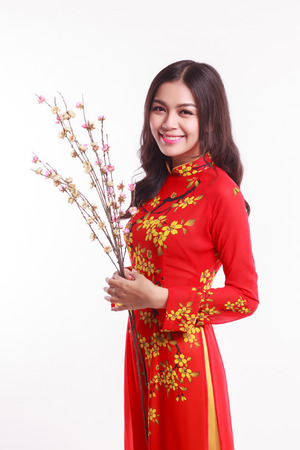 ao: Beautiful Vietnamese woman with red ao dai holding cherry blossom for celebrate lunar new year on white background