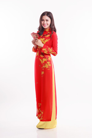 ao: Beautiful Vietnamese woman with ao dai holding lucky red packet for celebrate lunar new year on white background Stock Photo