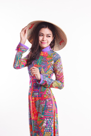 Beautiful Vietnamese young woman with tradition modern ao dai and palm-leaf conical hat ( non la ) on white background