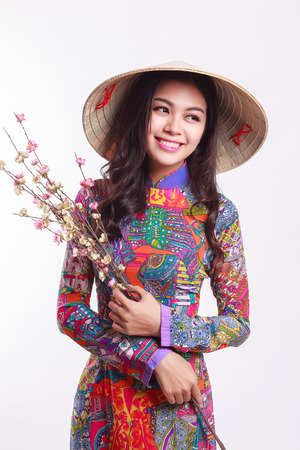 Beautiful Vietnamese young woman with tradition modern ao dai and palm-leaf conical hat ( non la ) holding cherry blossom at Tet Holiday