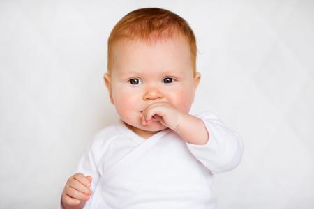 Little cute baby girl in white romper in bedroom. Stock Photo