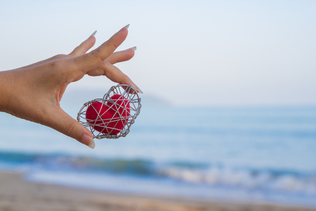 Hand that holds a strong red heart backdrop is the sea. Archivio Fotografico - 105042054