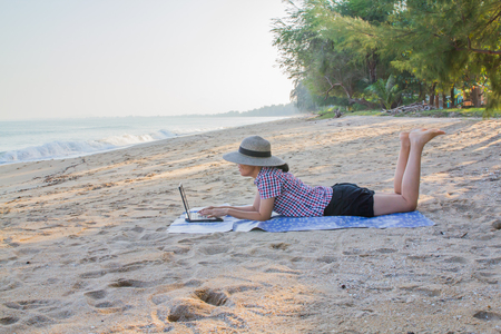 Women worked happily with the laptop on a beach.