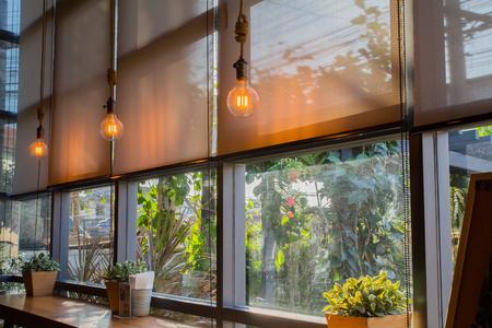 rolety chroniące przed słońcem i oświetlenie do dekoracji kawiarni.
