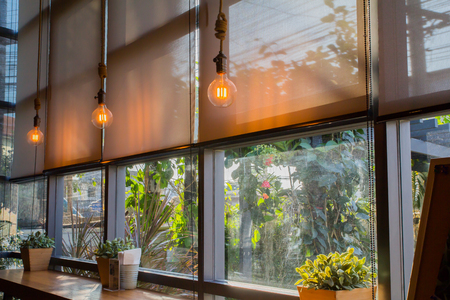 roll blinds to protect sunlight and lighting to decorate the coffee shop. 免版税图像