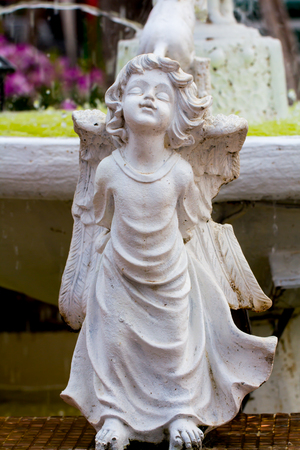white statue of winged child.