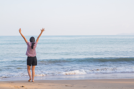 woman stretches her arms to the fresh air on the beach.