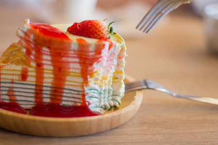 Crape cake dessert topped with sauce strawberry on wooden plate. Stock Photo