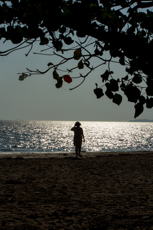 Woman on the beach at sunset and sparkle in the sea. Archivio Fotografico