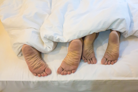 Human feet with white bed. 스톡 콘텐츠