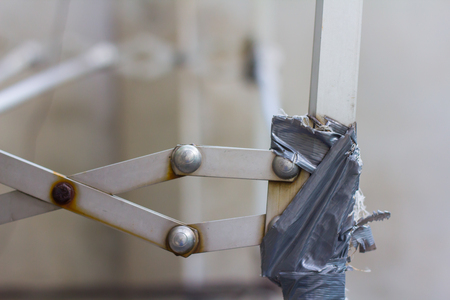 Closeup of broken clothes rack dryer aluminium that defective and use sticky tape wrapped up for repair.