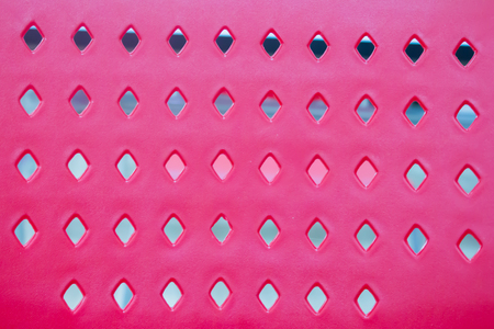 Pink plastic with pattern background hole. backrest part of chair.