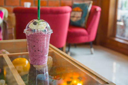 blueberry smoothie on the glass table in coffee shop. Archivio Fotografico