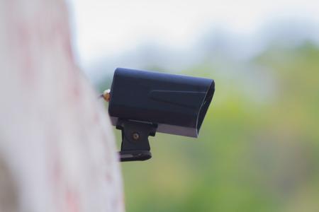 Black CCTV cameras in the green garden and blur background .
