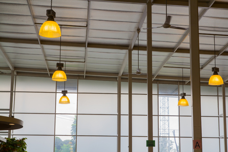 Yellow lamp hanging from the high ceiling. Archivio Fotografico - 104875683