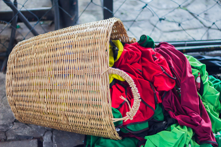 Rattan basket with bright color used clothes. Archivio Fotografico