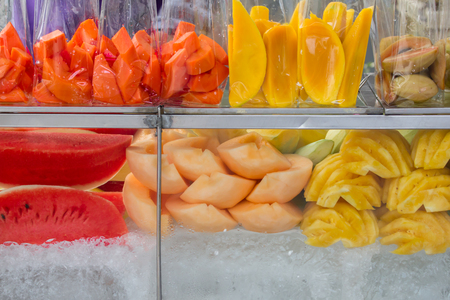 Thailand street food fruits in plastic bag ready for sale,Fresh mango,cantaloupe,lovelorn, pineapple, ripe papaya, watermelon and fruits slices in plastic bags, in a glass cabinet with ice at street market.