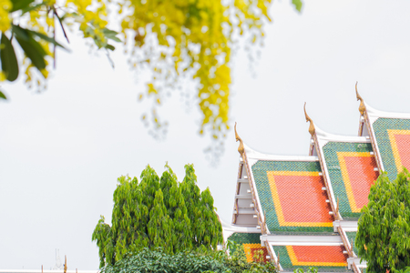 Temple roof and blurred image of beautiful yellow flowers. Archivio Fotografico