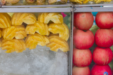 Thailand street food fruits in plastic bag ready for sale,Fresh pineapple, apples and fruits slices in plastic bags, in a glass cabinet with ice at street market. Archivio Fotografico