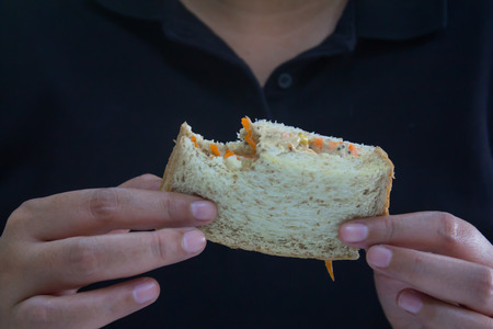 People wearing black t-shirts are eating delicious tuna sandwiches. Archivio Fotografico