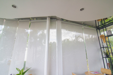 White curtain or blinds Roller sun protection and big Glass windows. Archivio Fotografico - 104550776