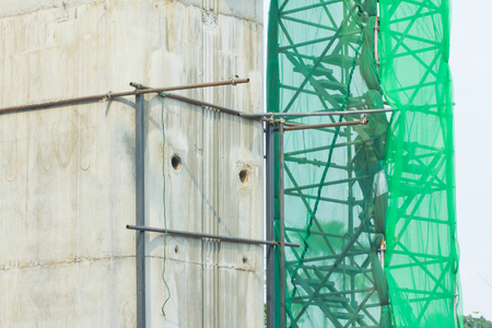 Pictures of large concrete pillars and scaffolding, netting cover for construction safety. Archivio Fotografico