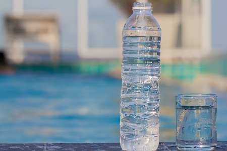 Glass of water and plastic water bottle by the pool.