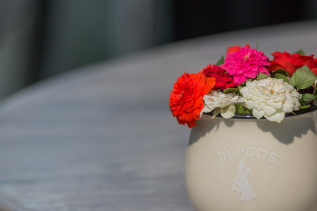 Colorful flowers in white cup vase on the table.