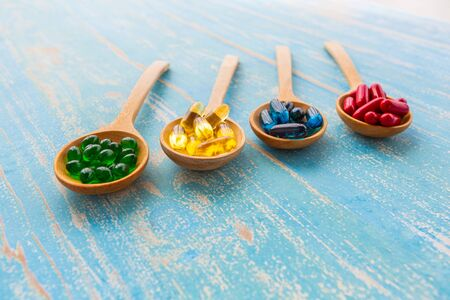 Closeup colorful soft gelatin capsules of food supplements in wooden spoon on vintage blue background