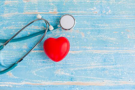 Closeup red heart and stethoscope on vintage wooden blue background Banco de Imagens
