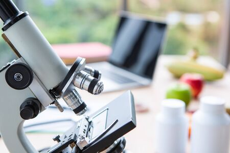 Closeup of microscope on nutritionist doctor table with labtop and fruits in laboratory room Фото со стока