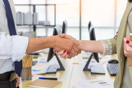 Asian man and woman shaking hands in partnership agreement on office room background