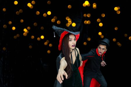 Witch woman escape from male vampire pulling her on dark background with yellow bubble bokeh - Asian young people in halloween party concept Reklamní fotografie