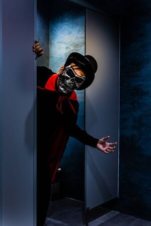 a man with metal skull mask and black hat in dim light toilet - Asian young people in halloween party concept Imagens
