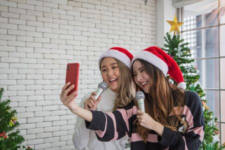 Beautiful two women with santa hat singing karaoke and selfie shooting with smartphone - Asian young people christmas party concept