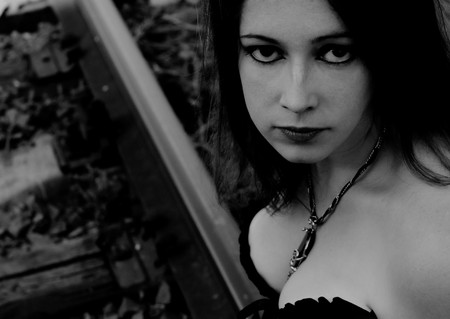 Close-up portrait of a beautiful gothic girl sitting on rails. Black and white photo
